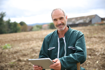 Farmer in field using digital tablet