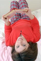 Joven mujer recostada leyendo un libro.