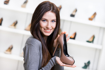 Portrait of woman keeping coffee-colored leather pump