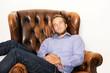 Junger Mann schläft auf Sessel