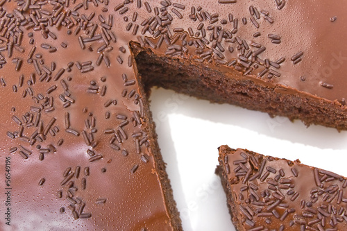 Sliced chocolate fudge cake isolated on white background.