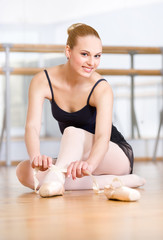 Sitting on the floor ballerina laces the ribbons of the pointes