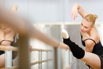 Ballerina stretches herself near barre and mirrors