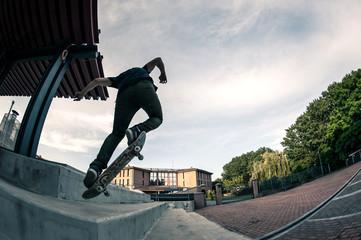 Skateboarder jump in the street from below.
