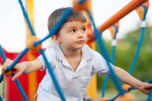 3 year old kid in a playground outdoor.