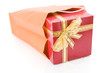 Red gift with a golden bow inside a shopping bag