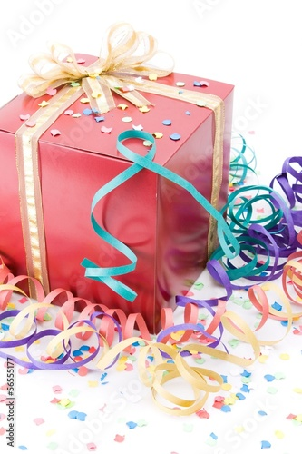 Red gift with a golden bow in a party setting