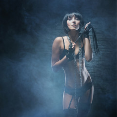 A young and sexy woman in fetish lingerie on a spooky background