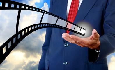 Film strip in businessman hand, Movie industrial