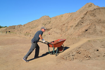 The elderly worker is lucky a wheelbarrow with soil on road cons