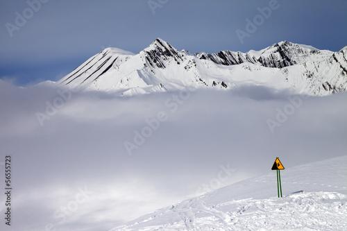 Warning sing on ski slope and mountains in fog