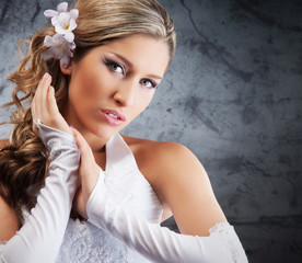 Portrait of a young and beautiful bride on a grey background