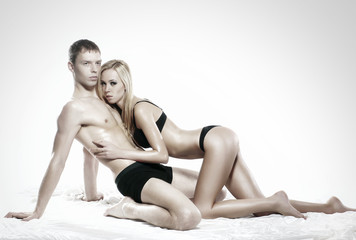 A young and sexy couple laying in black erotic lingerie