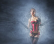 A young and sexy redhead cabaret dancer on a foggy backroung