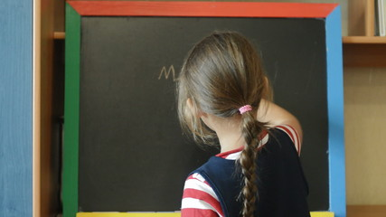 Schoolgirl draws on a chalk board
