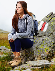 Woman hiker resting on a rock