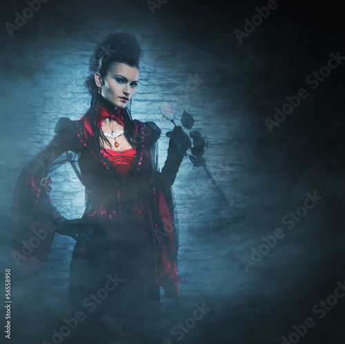 Halloween concept: a young and sexy lady vampire in the dungeon