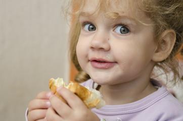 Маленькая девочка ест булку с задорным взглядом