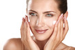 Leinwandbild Motiv beautiful model applying cosmetic cream treatmen on her face
