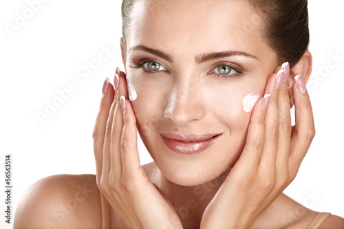 beautiful model applying cosmetic cream treatmen on her face - 56563514
