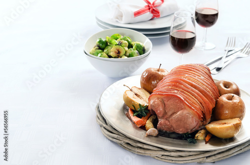Roast pork with apple on a table set for celebration