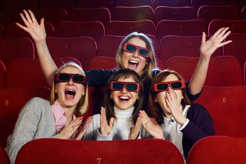 Group of excited  girls watching movie in cinema