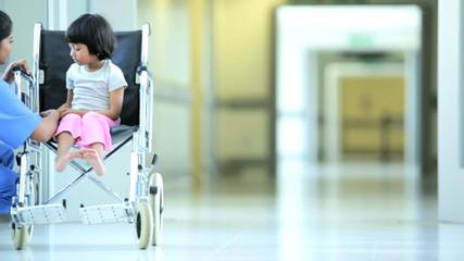 Ethnic Female Nurse Reassuring Young Child Patient