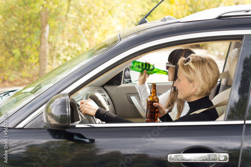 Two women driving a car while drinking