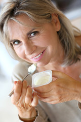 Portrait of senior woman eating yoghurt