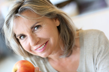 Portrait of senior woman eating apple