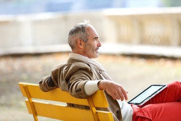Trendy senior man relaxing on bench with tablet
