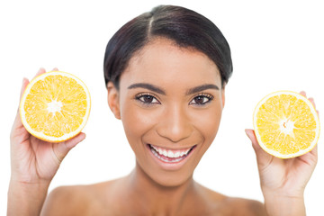 Natural attractive model holding slices of orange in both hands