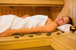 Peaceful brunette woman lying in a sauna