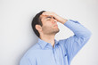 Irritated man with hand on forehead leaning against a wall