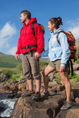 Couple standing at edge of river on a hike holding hands