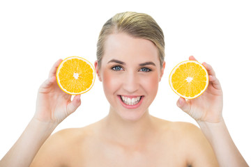 Smiling attractive blonde holding orange slices