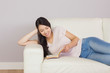 Pretty asian girl lying on the sofa reading book