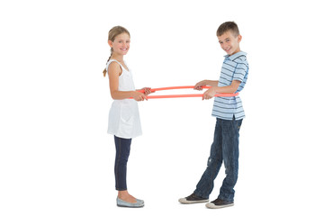 Cheerful brother and sister playing with hula hoop