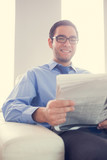 Content man looking at camera and holding a newspaper sitting on