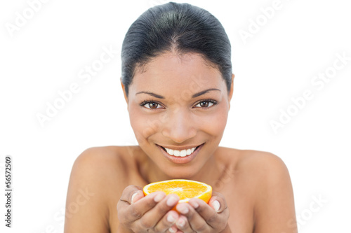 Smiling black haired model holding orange slice