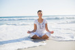Peaceful pretty woman in lotus position on the beach with wave r