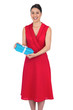 Smiling glamorous model in red dress holding present
