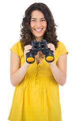 Cheerful casual young woman using binoculars