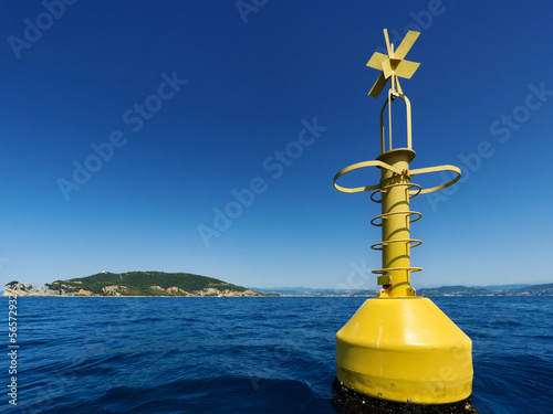 Yellow navigational buoy marker in sea
