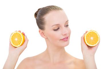 Peaceful pretty blonde model looking at an orange half
