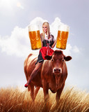 crazy tiroler or oktoberfest woman on a cow with beer