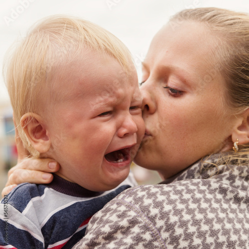 Portrait of a crying little boy who is being held by her mother