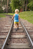 The little boy goes on railroad tracks