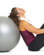 Tired fitness young woman sitting near fitness ball