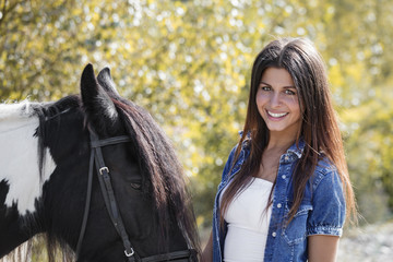 beautiful brunette girl smiling and embracing her horse